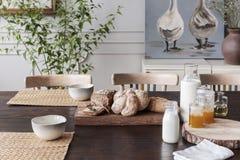 Ordeñe, miel y pan naturales en la tabla de madera de la cabaña en interior del comedor con el cartel Foto verdadera imagen de archivo