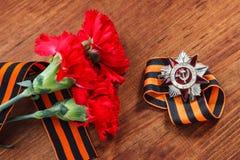 Orde van de patriottische oorlogs 1st klasse en twee rode anjers De dag van de overwinning 9 kunnen Selectief nadrukbeeld Royalty-vrije Stock Afbeeldingen