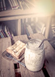 Ordeñe con la tostada en la tabla de madera con los libros Imagenes de archivo