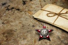 Ordem da estrela vermelha e de uma pilha de fotos velhas Imagem de Stock