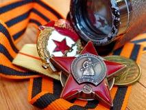 Ordem do ` e dos binóculos vermelhos da estrela do ` na fita do ` s de St George Cem gramas de vodca closeup heirloom memória Mai foto de stock