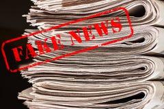 Orden fejkar nyheterna i röd text på tidningar royaltyfri foto