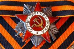 Orden soviética de la guerra patriótica de la inscripción patriótica de la guerra con la cinta del ` s de San Jorge 9 de mayo día Fotografía de archivo libre de regalías