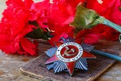 Orden soviética de la guerra patriótica de la inscripción patriótica de la guerra con los claveles rojos en una tabla de madera v fotografía de archivo