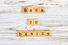 Orden tillbaka till grunderna som göras av bokstäver på träkvarter dra tillbaka till grunderna - grundprincipbegrepp Arkivfoto