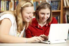 Ordenador adolescente del uso de las muchachas en biblioteca Fotos de archivo libres de regalías
