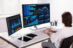 Ordenador de Analyzing Graphs On del agente del mercado de acción fotos de archivo