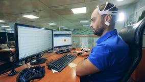 Ordenador de controles masculino del ingeniero usando las auriculares especiales de la exploración de la onda cerebral almacen de metraje de vídeo