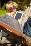 Ordenador de la PC de la tableta del hombre joven en parque o campus Fotos de archivo