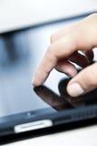 Ordenador de la tablilla con la mano Imágenes de archivo libres de regalías