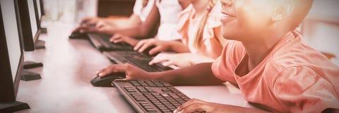 Ordenador de los niños en sala de clase fotos de archivo libres de regalías