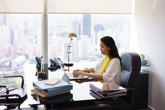 Ordenador de secretaria Typing On Laptop de la mujer de negocios en oficina fotografía de archivo