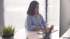 Ordenador de trabajo sonriente de la mujer asiática de los jóvenes hermosos en el escritorio en sala de estar en casa metrajes