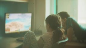 Ordenador del juego de niños en videojuegos los niños del muchacho y de la muchacha juegan la cámara lenta de los videojuegos en  almacen de video