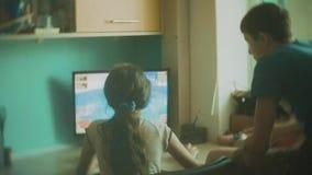 Ordenador del juego de niños en videojuegos los niños del muchacho y de la muchacha juegan la cámara lenta de los videojuegos en  metrajes