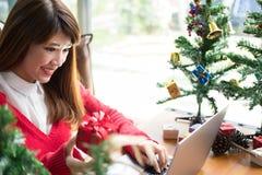 Ordenador del uso de la mujer en casa muchacha con la caja del presente del regalo para Chris Imagenes de archivo