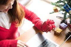 Ordenador del uso de la mujer en casa muchacha con la caja del presente del regalo para Chris Fotos de archivo libres de regalías