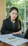Ordenador del uso de la mujer para el trabajo con el resumen del negocio o el informe del plan empresarial con las cartas y los g Foto de archivo libre de regalías