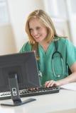 Ordenador feliz del doctor In Scrubs Using en el escritorio del hospital Foto de archivo