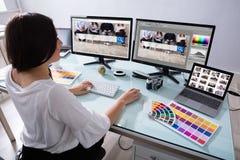 Ordenador femenino de Working On Multiple del diseñador fotografía de archivo libre de regalías