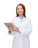 Ordenador femenino sonriente de la PC del doctor y de la tableta Foto de archivo libre de regalías