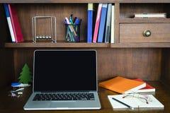 Ordenador, libros y algunos inmóviles en la tabla de madera Foto de archivo