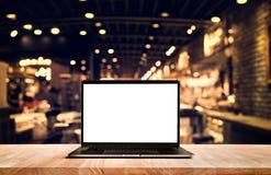 Ordenador moderno, ordenador portátil con la pantalla en blanco en tienda del café de la tabla foto de archivo