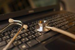 Ordenador o análisis de datos - estetoscopio sobre el teclado del cuaderno Imagen de archivo libre de regalías