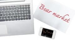 Ordenador, papel con el texto del mercado bajista y smartphone con el gráfico Foto de archivo libre de regalías