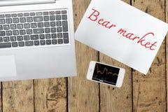 Ordenador, papel con el texto del mercado bajista y smartphone con el gráfico Imagenes de archivo