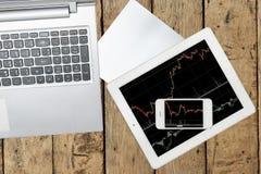 Ordenador, papel, smartphone y tableta con el gráfico en la tabla de madera Fotografía de archivo libre de regalías