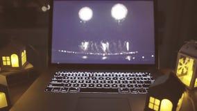 Ordenador portátil abierto con las velas del centelleo en la tabla almacen de metraje de vídeo
