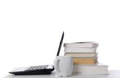 Ordenador portátil abierto, pila de libros y taza Foto de archivo libre de regalías