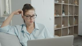 Ordenador portátil adolescente cansado del uso de la muchacha del estudiante en casa, mecanografiando en el cuaderno, preparándos almacen de metraje de vídeo