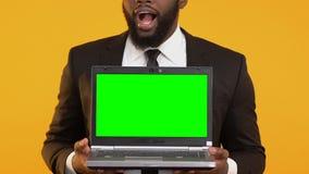 Ordenador portátil afroamericano emocionado de la demostración del encargado con la pantalla verde, oferta de trabajo en línea almacen de metraje de vídeo