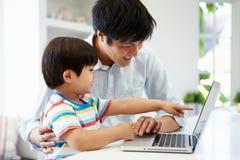 Ordenador portátil asiático del uso de Helping Son To del padre en casa fotos de archivo libres de regalías