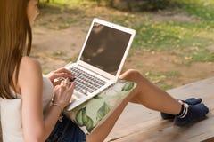 Ordenador portátil asiático hermoso del uso del adolescente de la mujer con la pantalla en blanco Imagenes de archivo