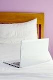 Ordenador portátil blanco en cama Fotos de archivo libres de regalías