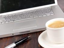 Ordenador portátil con café al lado de él Imagen de archivo libre de regalías