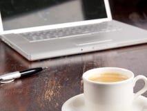 Ordenador portátil con café al lado de él Fotografía de archivo libre de regalías