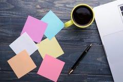 Ordenador portátil con café, la pluma y las notas sobre la tabla de madera Foto de archivo libre de regalías