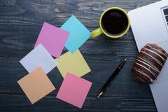 Ordenador portátil con café, la pluma y las notas sobre la tabla de madera Imágenes de archivo libres de regalías