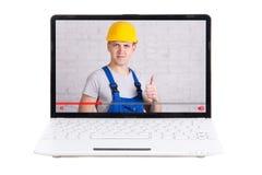 Ordenador portátil con el blog video sobre la construcción en la pantalla aislada encendido Imagen de archivo libre de regalías