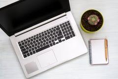 Ordenador portátil con el cactus y el cuaderno imagenes de archivo