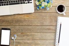 Ordenador portátil con el cuaderno del teléfono y la taza de café elegantes en etiqueta del lugar de trabajo Fotografía de archivo libre de regalías