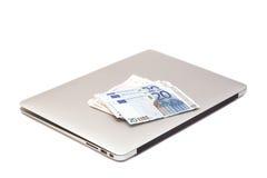 Ordenador portátil con el dinero euro Fotos de archivo