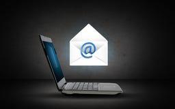 Ordenador portátil con el icono y la letra del email Fotografía de archivo