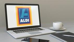 Ordenador portátil con el logotipo de Aldi en la pantalla Representación conceptual del editorial 3D del lugar de trabajo moderno Imagen de archivo