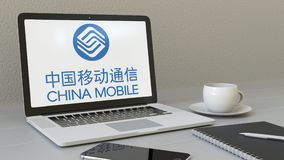Ordenador portátil con el logotipo de China Mobile en la pantalla Representación conceptual del editorial 3D del lugar de trabajo Foto de archivo libre de regalías
