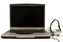 Ordenador portátil con el receptor de cabeza Foto de archivo libre de regalías